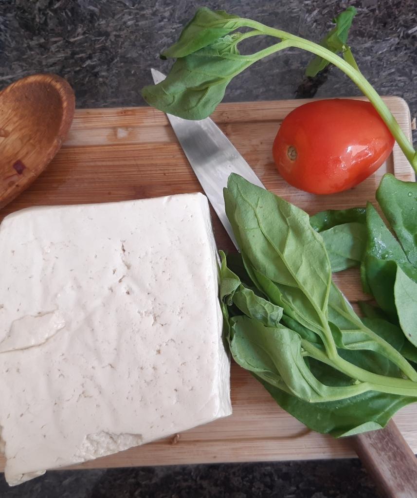 Peça de tofu na tábua com um maço de espinafre do lado, um tomate e a faca