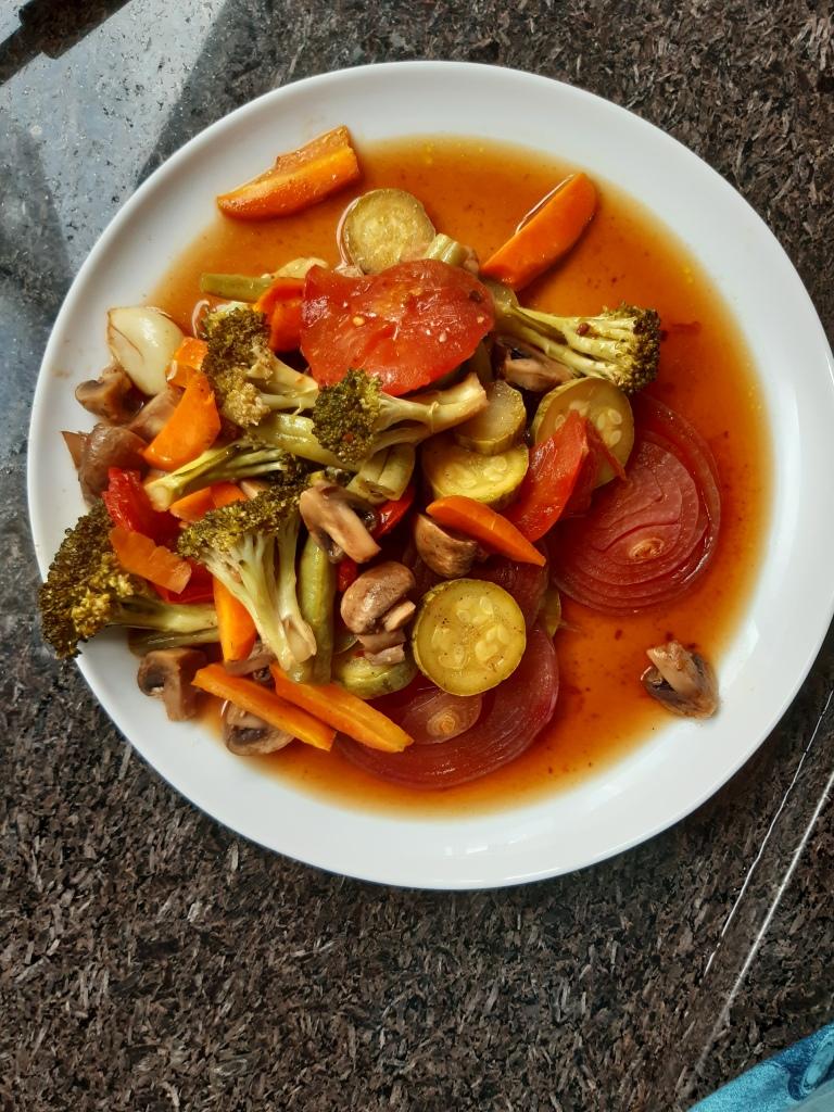 prato branco raso cheio de cenoura, brócolis, cogumelo, cebola, tomates suculentos, com caldo escorrendo