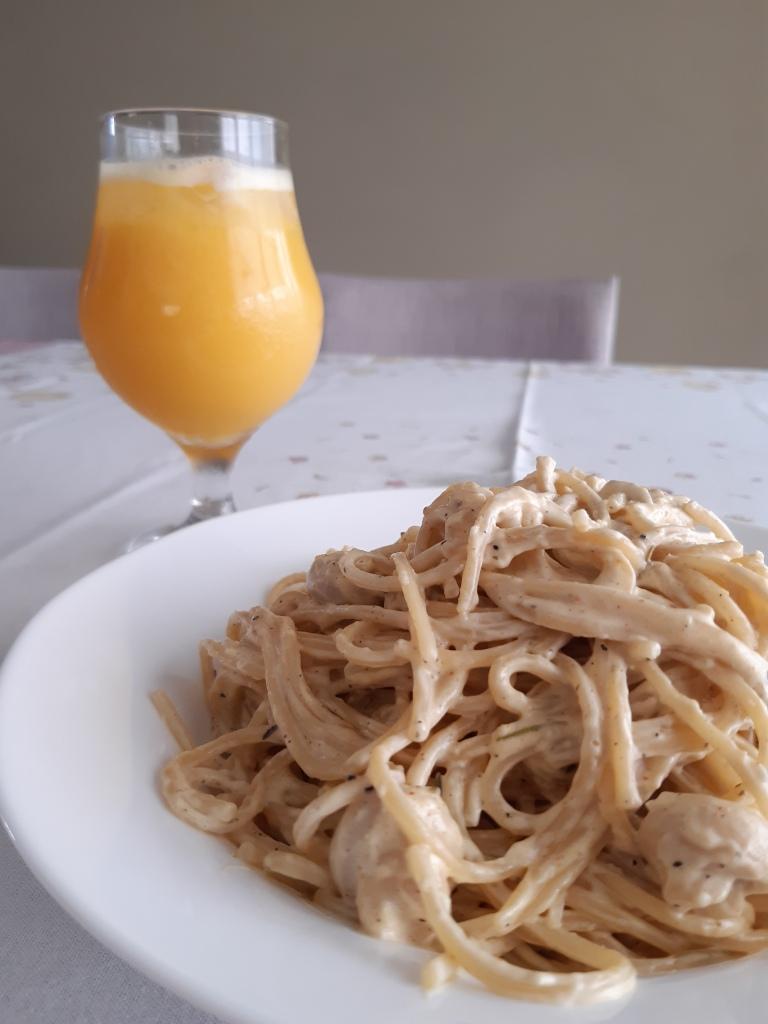 prato fundo cheio de macarrão espaguete com molho branco e uma taça cheia de suco de laranja em uma mesa de toalha branca